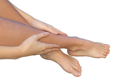 Woman holds her leg with fingers of her hands. Side view on female lower leg touched by the fingers of a woman. A barefoot woman is touching her lower leg Royalty Free Stock Images