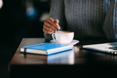 Woman holds hot cup of coffee, warming her hands Stock Image