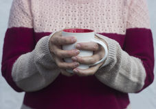 A woman holds a hot cup of tea and warms his hands. Stock Photo