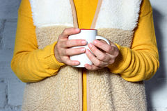 Woman holds a hot cup of tea and warms his hands.  Stock Photo