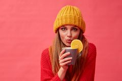 Beautiful girl holds a hot drink with orange. Red background. Studio. Woman holds a hot drink with orange. Red background. Studio stock photos