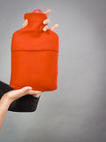 Woman holds hot water bottle in red fleece cover Stock Photo