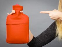 Woman holds hot water bottle in red fleece cover Royalty Free Stock Image