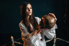 Woman holds human skull in hand, dark magic, witch. Young woman in white shirt holds human skull in hand, pentagram circle with candles, smoke all around, witch stock photography