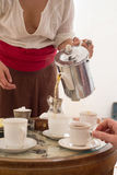Woman holds a kettle and poured tea into cups Royalty Free Stock Photo