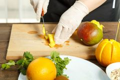 The woman holds a knife in the hand and cuts a mango fruit on pieces on a wooden board. horizontal image. stock images