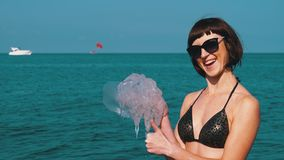 Woman holds a large sea jellyfish against the backdrop of the black sea. Rhizostoma