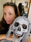 Woman holds laughing ghoul skeleton decor stock photography