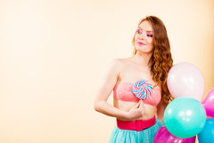 Woman holds lollipop candy and balloons Royalty Free Stock Photos