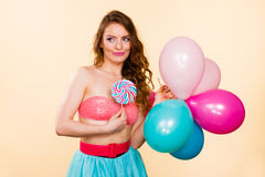Woman holds lollipop candy and balloons Royalty Free Stock Photography