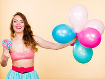 Woman holds lollipop candy and balloons Royalty Free Stock Photo
