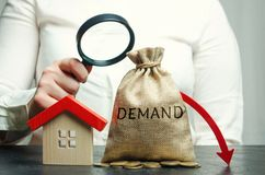 A woman holds a magnifying glass over a money bag with the word demand, a down arrow and house. The concept of low demand for the stock photos