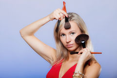 Woman holds make-up brushes near face. Stock Photo