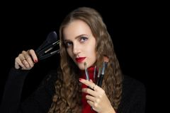 Woman holds makeup brushes in her hands royalty free stock images