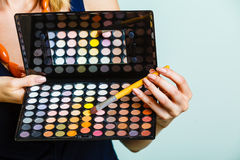 Woman holds makeup eye shadows palette and brush. Royalty Free Stock Photos