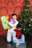 Woman holds many gifts at floor near Christmas tree and smiles Stock Photo