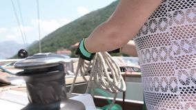 Woman holds a marine rope, folds it on the deck of the yacht stock video footage