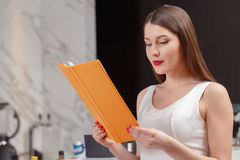 Woman holds a menu at the bar Stock Photo