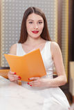 Woman holds a menu at the bar Stock Photography