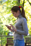 The woman holds the mobile phone in hand Stock Photography
