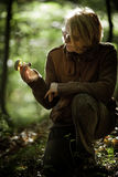 Woman holds a mushroom she has harvested. In the forest Royalty Free Stock Image
