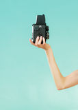 Woman holds old camera on blue Royalty Free Stock Photos