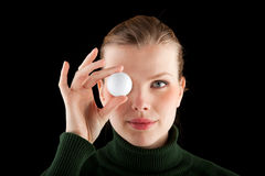 Woman holds one golf ball in front of her eye Royalty Free Stock Photos