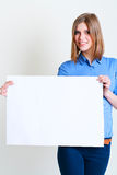 Woman holds out a big blank card Stock Images