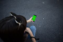 Woman holds phone with chroma key. Over head shot of woman in jeans and with sunglasses holds smartphone with green chroma key screen, place for your image or Stock Images