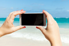 Woman holds phone for taking beach photo Royalty Free Stock Photo