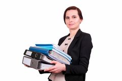 The woman holds a pile of folders. The business woman the brunette keeps a pile of folders with documents in a jacket, on the isolated white background. A Stock Photo