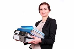 The woman holds a pile of folders. The business woman the brunette keeps a pile of folders with documents in a jacket, on the isolated white background. A Royalty Free Stock Photos