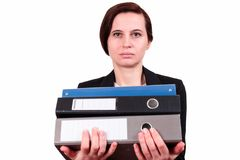 The woman holds a pile of folders. The business woman the brunette keeps a pile of folders with documents in a jacket, on the isolated white background. A Royalty Free Stock Photo
