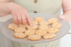 Woman holds a plate with biscuits Stock Photo