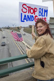 Woman holds political sign on overpass. Royalty Free Stock Photos