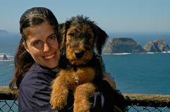 Woman holds puppy by ocean Royalty Free Stock Image