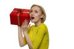 Woman holds red box on white background.