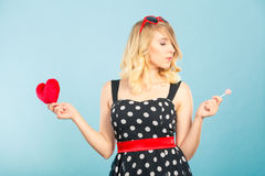 Woman holds red heart love symbol and lollipop candy Royalty Free Stock Image