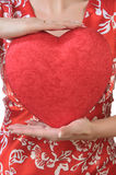Woman holds a red heart opposite the bust. Young woman in red holds a red heart opposite the bust. Without of face Stock Images