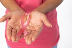 Woman holds ribbon in both hands for breast cancer awareness. Woman hold ribbon in both hands for breast cancer awareness against white background stock image