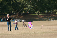 Woman Holds Ropes And Steers Kite At Autumn Festival Royalty Free Stock Photo