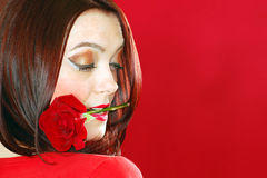 Woman holds rose in mouth. The woman holds a red rose in mouth on red background Royalty Free Stock Photo