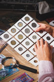 Woman holds a set of old coins in the pockets Royalty Free Stock Photos