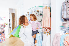 Woman holds shopping bags with her small daughter Stock Images