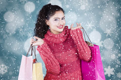 Woman holds shopping bags with winter background Stock Photos