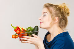 Woman holds shopping basket with vegetables, smelling Royalty Free Stock Images