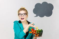 Woman holds shopping cart with vegetables, copy space Royalty Free Stock Photo