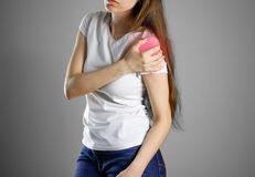 A woman holds the shoulder. The pain in my arm. Sore point highlighted in red. Closeup. Isolated royalty free stock image