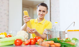 Woman shows uncooked pasta Royalty Free Stock Photography