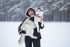 Woman holds Siberian Husky on her arms. Royalty Free Stock Photos